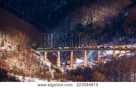 train over viaduct in winter mountains. lovely transportation scenery with snowy forested hills