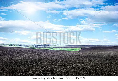 Field plowed, sown cereals. Plowed field in spring day. Black soil plowed field. Plowed field in the blue sky.