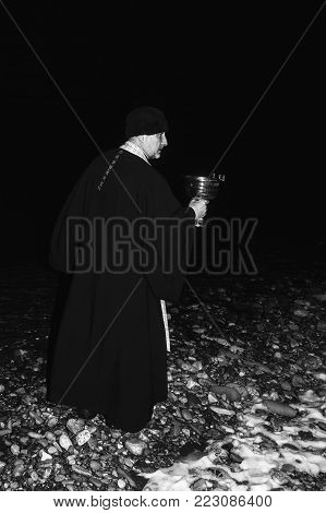 Adygea, Russia - January 19, 2018: an Orthodox priest blesses the water in the river the night of the feast of the Epiphany, a black and white photo