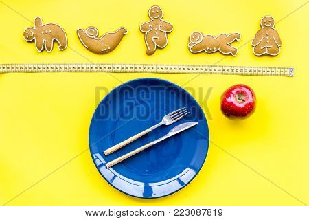 Yoga and healthy diet for lose weight. Plate and cookies in shape of yoga asans on bright yellow background top view.