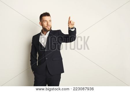 Handsome young caucasian businessman posing in studio and pointing up with finger on white background. Confident serious man in formal clothes, copy space
