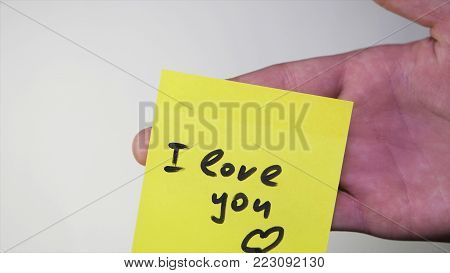 Note with I love you. Blank yellow sticky note with I love you sign pined on a cork bulletin board. Inscription on the sticker I love you on white background. Man's hand put blank yellow sticker isolated on a white background