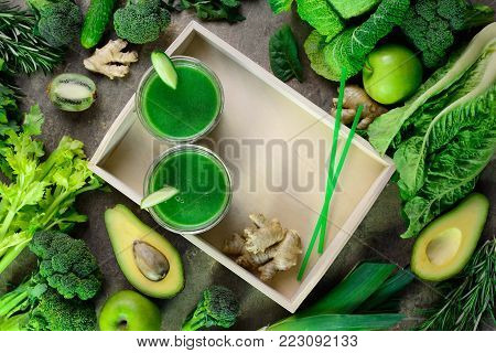 Detox green smoothies concept, two glasses of green diet detox drink  and various fresh green vegetables around them, view from above composition with a space for a text