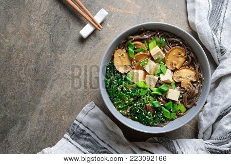 Diet vegetarian bowl of soba noodle soup rich with various sources of vegan protein such as mushrooms, tofu and kale; the meal seasoned with sesame seeds and chives. View from above arrangement.