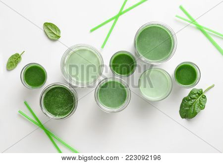 Detox green smoothies concept, various glasses of green diet detox drinks, view from above