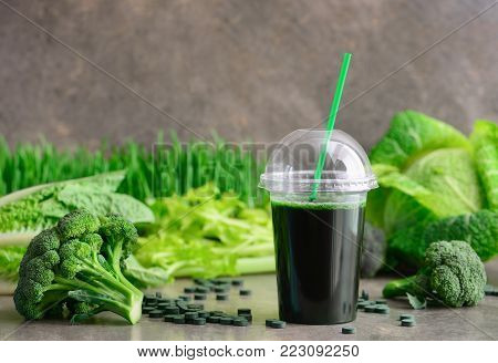 Detox green smoothies concept, a glass of green diet detox drink and various fresh green vegetables such as broccoli and spirulina pills behind, front view