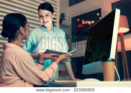 Fresh ideas. Two upbeat young female office workers sharing ideas during the break at work and showing each other something on their devices