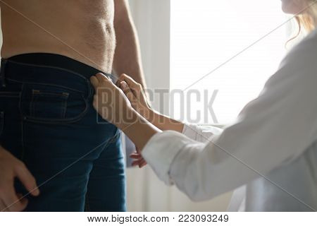 Close-up picture of woman unzipping mans pants in bedroom