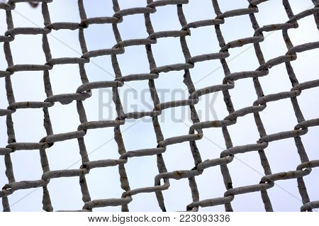 Landscape view number two of a network of thick twisted and knotted silver wire forming an abstract composition that is set against a pale blue sky.