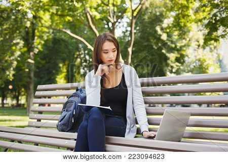Pensive student girl sitting on bench in park, working with laptop and taking notes, preparing for exams outdoors, having rest in university campus, copy space