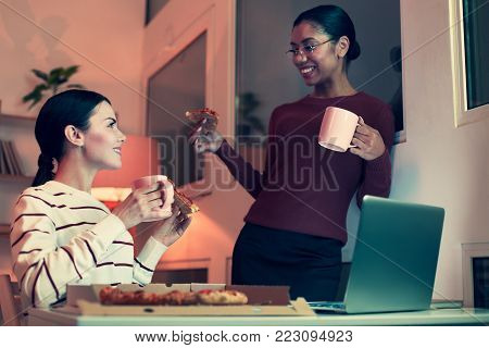 Best friends. Two upbeat female friends eating pizza and drinking tea while talking to each other during the sleepover party