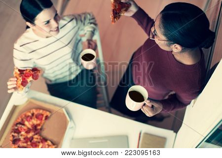 Favorite food. The top view of two upbeat young female friends eating pizza and drinking tea while talking to each other