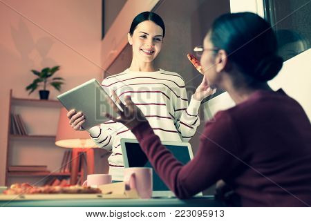 Non-formal ambience. Two pleasant female colleagues eating pizza and talking to each other, discussing work, while one of them holding a tablet