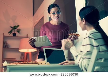 Informal ambience. Two charming female colleagues eating pizza and drinking tea while discussing their common project