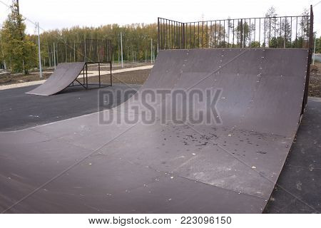 street skating in open skate Park.Extreme skating in a concrete skatepark outside.Skateboarder does an extreme sport