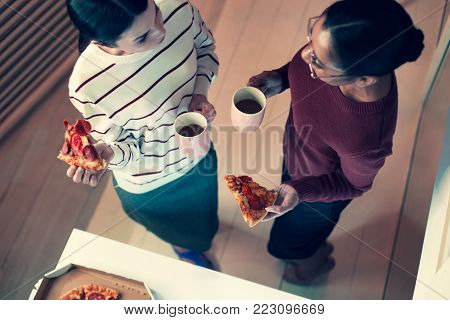 Delicious snack. The top view of two charming young woman enjoying pizza and drinking tea while chatting with each other