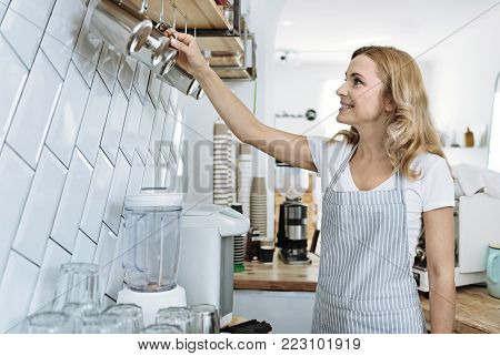 Take this one. Attractive female turning her head and raising right arm while standing in the kitchen