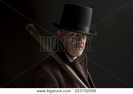 Portrait of a sinister thug wearing a top hat with a wooden bat