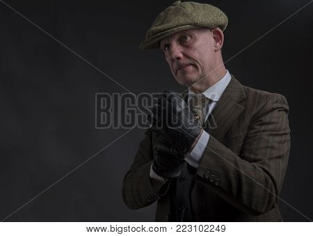 Portrait of a mature gangster holding his fists up ready to fight, taken with copy space