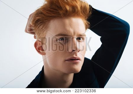 Handsome boy. Good-looking stony-faced red-headed young man wearing a black jacket and touching his head and staring