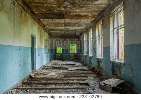 The Ruined Long Corridor Of Abandoned School After Chernobyl Disaster In Evacuation Zone. Consequences Of The Nuclear Pollution Twenty Years Later.