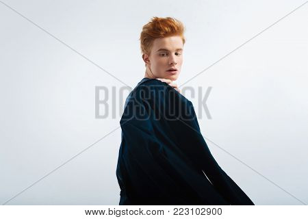 Stylish. Good-looking unsmiling red-haired young man wearing a black jacket on his shoulder and thinking and looking over his shoulder