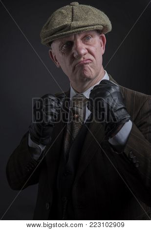 Portrait of a mature gangster holding his fists up ready to fight