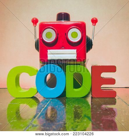 retro red robot head and the word CODE on a old wooden floor
