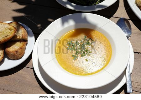 Fish soup dish from red scorpionfish next to bread, greens salad on wooden table in the greek tavern. Horizontal. Close-up. View from above. Daylight.