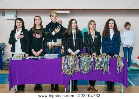Kamenskoye, Ukraine - March 9, 2017: Championship of the city of Kamenskoye in cheerleading among solos, duets and teams, Judges listen to the anthem of Ukraine before the award ceremony