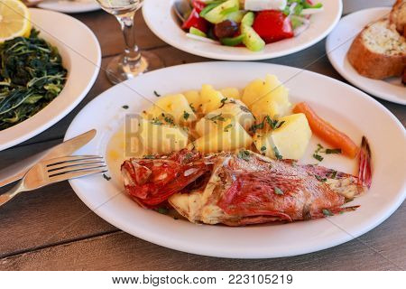 Cooked fresh red scorpionfish sarved with boiled potatoes on white plate near glass of white wine, greens and greek salads dishes, bread on wooden table in greek tavern. Horizontal. Close-up.