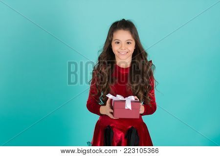 Girl with long brunette hair smile with present. Happy child in red dress hold box on blue background. Gift giving, celebration. Birthday, new year, christmas holidays. Boxing day concept, copy space