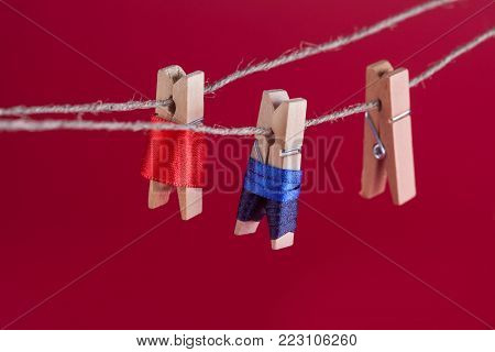 Funny peg characters and clothesline. Man in suit, woman red dress. wooden clothespins macro view, shallow depth of field.