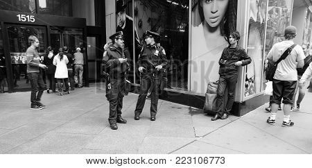 New York, USA - November 13, 2008: two american policewomen police officers, in uniforms patrolling city street at daytime on cityscape background. Public safety