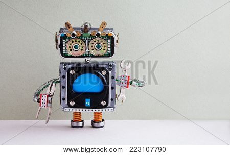 Fixing computer concept. Robotic handyman hand wrench pliers. Colorful display robot toy, empty blue monitor. Maintenance service works concept. Gray paper background, copy space