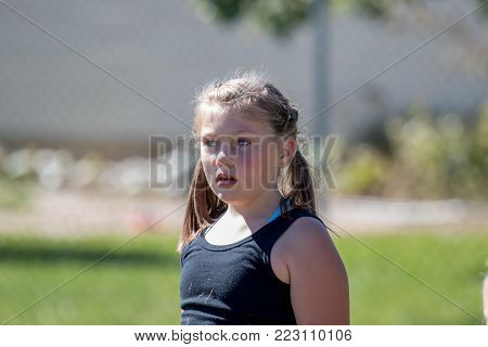 Cute young girl with pigtails playing outside on a sunny day and blurred background.