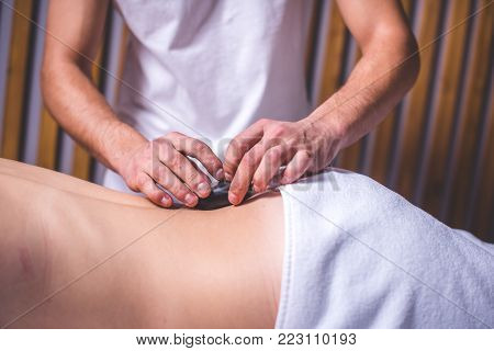 Men's hands lay a dark hot stone on the client's back. The person lies sideways to the camera. The lower part of the body is covered with a white towel. Stone therapy.