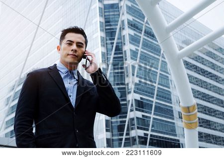 young smart asian business man wearing modern black suit making phone call with mobile smart phone in building city background, internet network connection, technology communication, financial concept