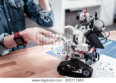 Modern gadget. Little robot staying in semi position on the table while being ready for usage