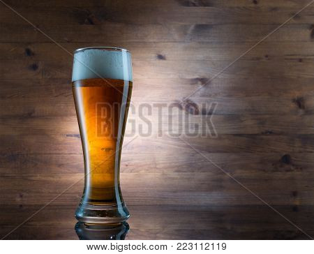 Glass of golden beer on wood background