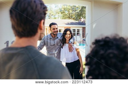 Excited african woman attending a friend's housewarming party. Woman giving a wine bottle to couple outdoors.