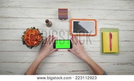 woman takes a smartphone from a white wooden desk and typing using app. Nearby are flowers and an orange digital tablet. Chroma key Green screen. Top view. Hands close up view.