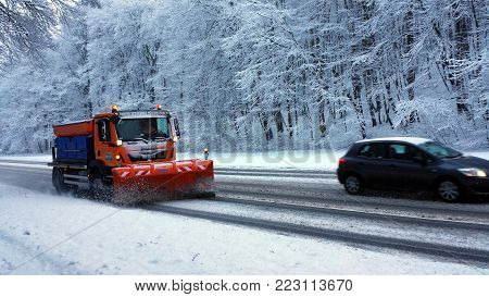 Gdynia, Poland - January 21, 2018: The snow plow clears the road in the snowy forest.