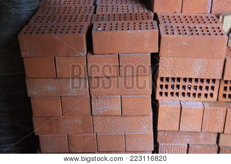 Stack of red hollow facing bricks with square holes foreground closeup