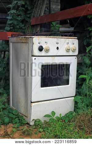 very old white gas stove sitting on the green lawn