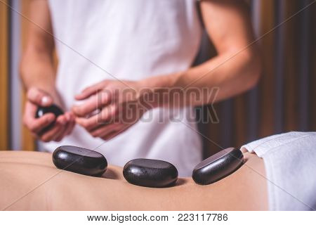 The masseur holds a hot stone for stone therapy. Dark hot stones lie along the back of the spine. The masseur conducts stone therapy. Background is blurred. The lower part of the body is covered with a white towel.