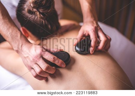 The male hands of the masseur lay hot stones on the girl's shoulder blades. Hot stones lie on the back of a woman. The girl's hair is gathered in a bun. Stone therapy.