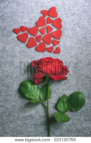 Red rose and a heart from little red hearts - Red rose and a heart from little red hearts - Valentine day image with a beautiful red rose and small red fabric hearts displayed in a shape of a big heart, on a vintage grey fabric background.