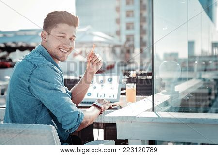 Education is the key to success. Handsome guy turning his head into the camera and grinning broadly while sitting on a cafe terrace and working on his home assignment.