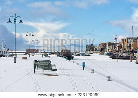 Dutch harbor of fishing village Urk in winter time. The water is frozen and covered with snow.